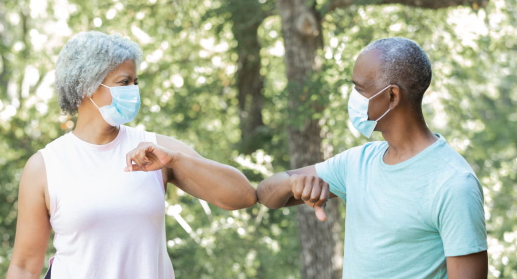 Elderly People In Masks Elbow Bumping